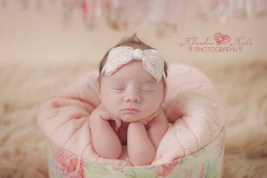 Pink satin bow wrapped in lace with pearl on a soft elastic headband